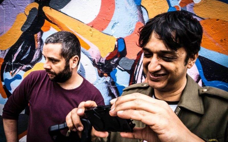 2 homens próximos a uma parede, um deles fotografando como celular