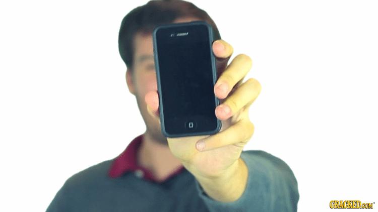 Homem segurando iPhone em frente do rosto, em close