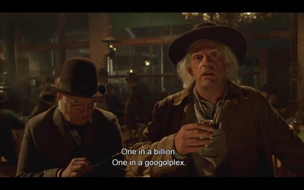 Dois homens de chapéu, um deles melancólico com copo de bebida alcoólica na mão