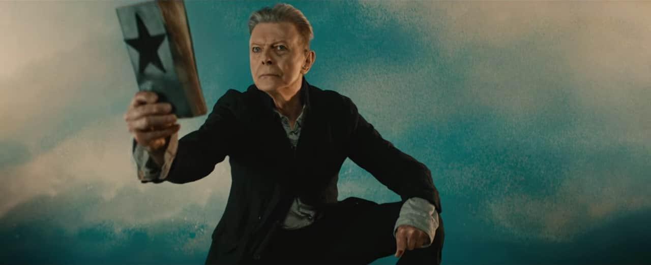 David Bowie agachado segura um livro, como escritura sagrada