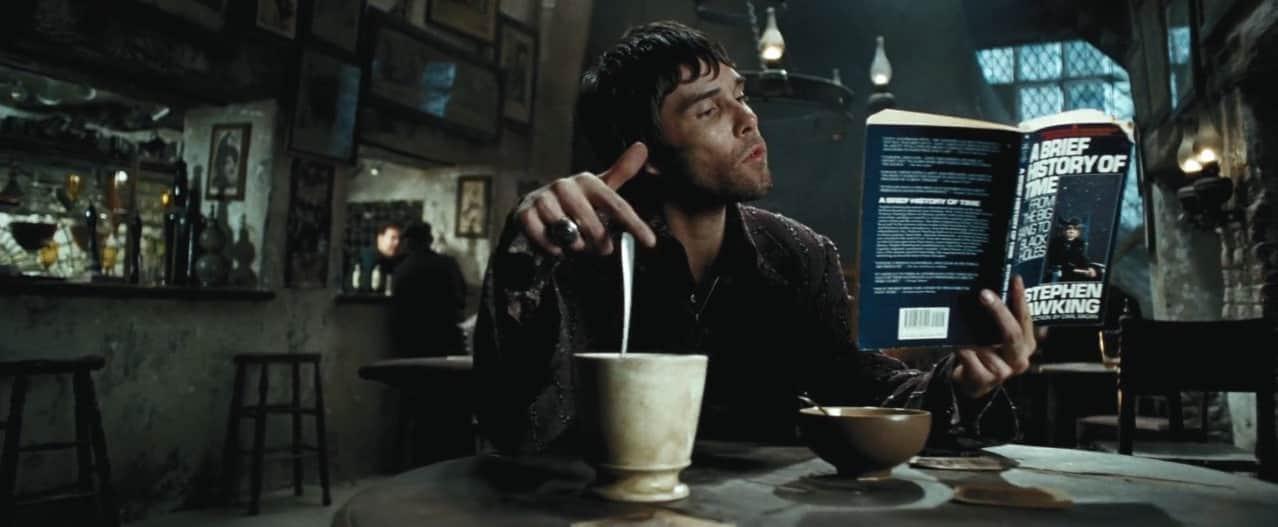 rapaz sentado em mesa mexe o café sem tocar na colher enquanto lê livro A Brief History of Time