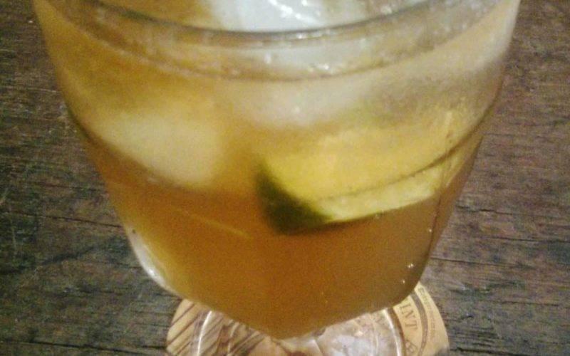 traça de vidro com bebida com bastante gelo e limão, sobre mesa de madeira