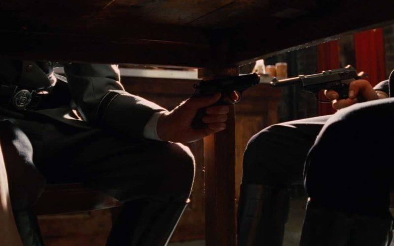 abaixo de uma mesa, dois homens seguram armas um contra o outro