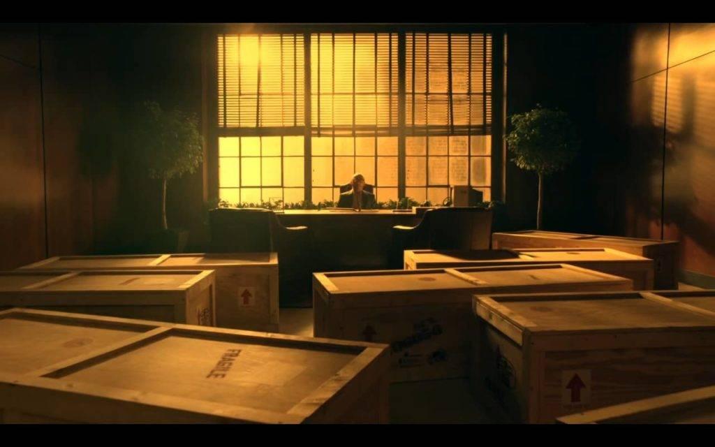 numa grande sala, diversos caixotes, parecendo caixões funerários, dispostos em frente a mesa de um homem de meia idade