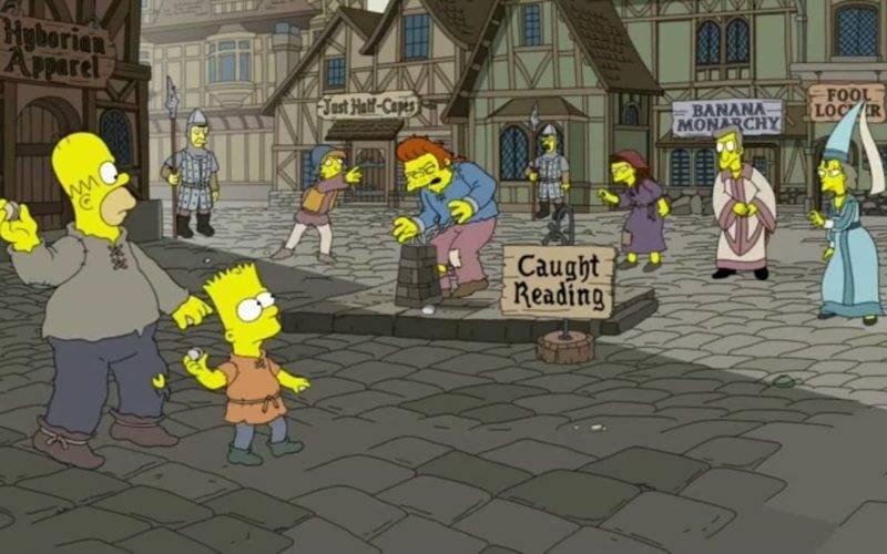 """Homer, Bart e outros moradores do vilarejo medieval jogam pedra em homem acorrentado com a placa """"Pego Lendo"""""""