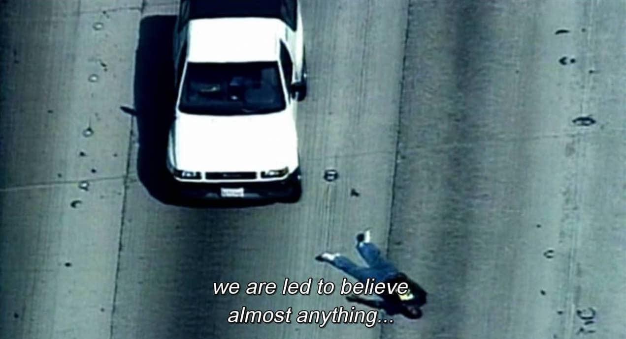 Tela de TV mostra carro em autoestrada e corpo ao lado, com os dizeres We are led to believe almost anything...