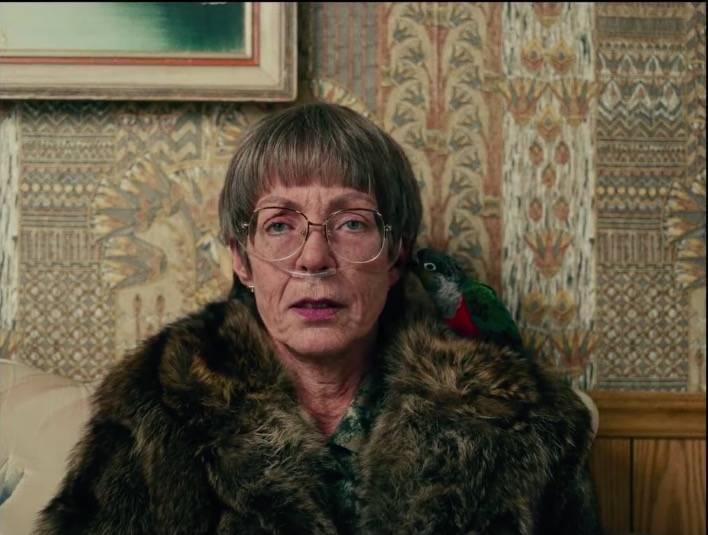 Mulher idosa com casaco de pele e um piriquito no ombro