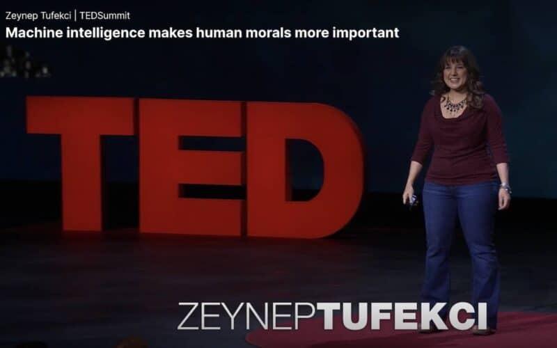 Uma mulher em um palco, vista de corpo inteiro, vestida com blusa roxa e calça jeans, com os braços ao seu lado, estendidos. Ao fundo do palco, as letras TED esculpiadas com cerca de um metro de altura cada, na cor vermelha.